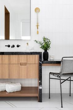 Transitional bathroom boasting a black marble top drop down makeup vanity with a gray and black industrial chair. Black Marble, Marble Top, Wall Mounted Kitchen Shelves, Garage Door Styles, White Wall Tiles, Industrial Chair, Industrial Bathroom, Transitional Bathroom, Weathered Oak