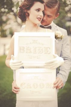 bride and groom holding signs // photo by GideonPhoto.com