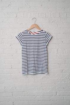 A perfectly classic white and navy stripe tee with small cuffed sleeves and a not too tight, not too loose fit. - 100% Cotton - Machine Wash Warm - Size 2 shown in picture