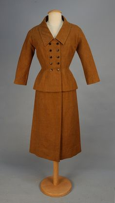"""1940s JACQUES FATH LIGHTWEIGHT WOOL SUIT. Nut brown wasp waisted jacket having narrow double breast with ten black buttons, wide collared V-neck, 3/4 sleeve, princess seams, peplum, narrow skirt with back zipper, black silk lining. Label """"Jacques Fath Paris"""". Tape label inked with """"XBM"""" stapled in sleeve. B-36, Sh-17, Slv-23, Skirt W-24, L-28."""