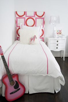 Hot white and pink girl's bedroom features a hot pink geometric print headboard upholstered in Victoria Hagan Summer Squares Fabric on twin bed layered with pink grosgrain trimmed bedding which pairs with a Mongolian wool pillow layered behind a pink zebra pillow over a white pleated bed skirt.