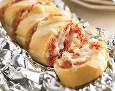 Grilled Italian Stuffed French Bread Recipe - Make extra of this crowd pleasing cheesy pesto French bread for you next grill out. Your family will be happy you did. #Schwans #EasyRecipes #Inspiration