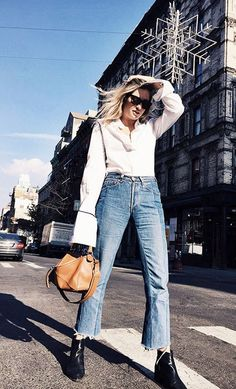 A button-down shirt is paired with vintage jeans, boots, and a Loewe Puzzle bag