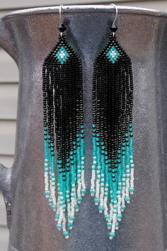 Black, iridescent green, light alabaster, and luster ecru seed beads make up these long fringe earrings. They are 4 1/4 long (including