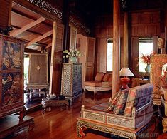Traditional Thai house with old manuscript cabinet, table, and silk cushions in teak living room in Thailand, Southeast Asia, Asia