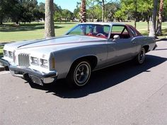 Mine looked exactly like this one!!!    I really wish I had her back!!!  1977 Pontiac Grand Prix  with red vinyl bucket seats & a cassette player.  Google Image Result for http://images1.americanlisted.com/nlarge/1977_pontiac_grand_prix_27945307.jpg