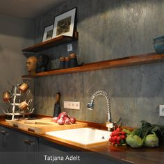 Mit viel Liebe zum Detail wurden graue Hochglanz Küchenfronten und warme…