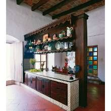 In the kitchen, a counter with overhead shelving divides the cooking and eating areas. A stained-glass window is visible in the background.