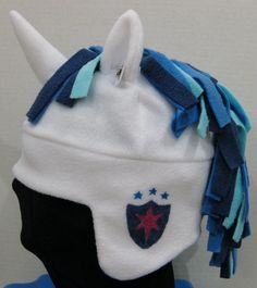 Fleece aviator ear hat with 3D horse ears, 5 inch multi colored mane, and a hand-stenciled cutimark. Cosplay hat of Shining Armor (copyright Hasbro), a recurring character of the television show My Little Pony: Friendship is Magic. The aviator hat has a white base, plush unicorn horn, multicolored mane, and a navy, blue, and pink shield cutimark.