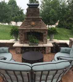 Awesome outdoor fireplace with seating wall and decorative concrete patio in Lee's Summit! #patio #patiolife #outdoorliving #outdoorfireplace #hinklehardscapes