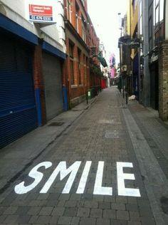 Participación Eduardo Bustillo: Esta foto está tomada en una calle de Dublín (Irlanda). Se trata de una intervención urbana en la que se recuerda al ciudadano que hay que tener una actitud positiva al enfrentarse cada día la ciudad. SMILE!! No puedo sino sonreír! Me reí cuando lo vi, y me río cada vez que veo la foto! Creo que viene que ni pintada para este concurso.