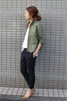 Summer casual style with an olive field jacket, relaxed white tshirt, black ankle pants, and tan pointed kitten heels.