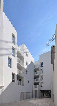 Social Housing in Paris / Bigoni Mortemard Architects patio appartementen wit borstwering CBO