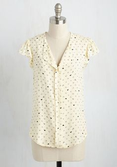 Gleefully scrolling through your premier website, you celebrate your blossoming career as a graphic designer in this ivory top. With a folded V-neckline, ruffled sleeves, and a pleated back, this scribbly heart-printed top is the perfect expression of your blossoming love of your craft!