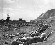 US Marines burrowing in the volcanic sand on the beach of Iwo Jima Japan 20 February 1945. Note LSM-264 and Mount Suribachi in background.