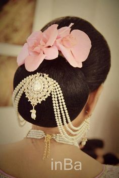What a beautiful low bun with ornamental chains linked to earings! Care however should be taken before adopting such hairstyles, as due to it's high static charge, it will cause phlegm to move up in the throat, causing the voice to quaver & a frequent urge to clear the throat. A heavy chabi chhalla with a long & wide hook if inserted at the edge of the pleats of the saree, will reduce this problem as it's hook will activate the acupressure points that act to keep the throat clear.