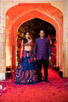 Sangeet Lehengas - Manav & Sareena wedding story | WedMeGood | Bride in a Blue Lehenga with Pink and Red Embroidery and a Translucent Blouse and the Groom in a Purple Sherwani #wedmegood #realwedding #sherwani #lehenga #bridal #sangeetlehenga #bridalwear #groomwear #coupleshot