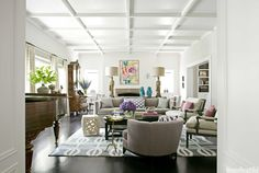 """""""Float furniture away from the walls: It creates more intimate seating,"""" designer Betsy Burnham says. She did just that in the living room of this California house. The console table separating back-to-back sofas is decked with vintage goddess figurine lamps and Chinese monkeys """"for a Tony Duquette, William Haines flavor."""" Sellarsbrook rug, the Rug Company. Rectangular Cocktail Table, Baker. Amy Neunsinger  - HouseBeautiful.com"""