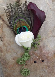 I love peacock feathers and I love calla lilies for corsages! I am glad when my Bride that got married this past Saturday wanted to use both! For the Groom a bleached peacock feather was used with …