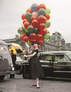 Audrey Hepburn, wearing Givenchy, poses on location during the filming of Funny Face (1957) at the Jardin des Tuileries.