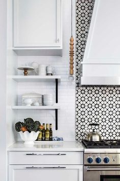 Gorgeous black and white mosaic cooktop tiles are positioned behind a white wood clad hood mounted above a stainless steel oven range. Deco Cuban Star tiles from www.decobella.co.za