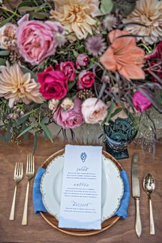 Wedding centerpiece with loose, jewel tone flowers and blue and gold table setting.