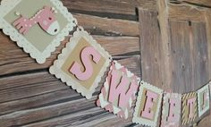 This ADORABLE Giraffe-themed Sweet Baby banner is the perfect accent for your baby shower! The lettering is cut from a pink card stock and is 3D mounted on a mix of creams, tans and light brown squares. The background squares are premium printed card stock of varying patterns that all came from the same book. Also, includes three adorable multi-layered die-cut giraffes. Die-cut giraffes are mounted with 3-D foam mounts for a pop-off-the-page effect. The banner is strung together with pink…