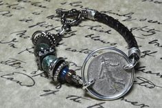 French coin bracelet with leather braided cord and toggle clasp.