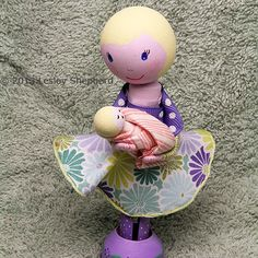 A clothespin doll holds a baby doll made from beads. If you want to make a clothespin doll baby and mum for a shower decorations or cake topper for a new mum, it is easy to make a newborn baby doll to fit in her arms. To make the baby shown here, I glued a round wooden bead to the top of a vase shaped wooden bead.....