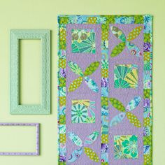 Simple squares and curved appliqués in bright prints pop off a coordinating  solid to create a dynamic wall hanging.