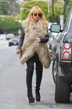 faux fur vest over a leather jacket with knee high boots