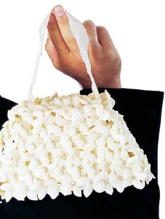 Purse-Style Bouquet  This purse-inspired bouquet would set off a contemporary-style dress nicely. Pearl-head pins adhere white stephanotises to a fabric-wrapped trapezoid cut from plastic foam. A coordinating ribbon pinned to the top of the arrangement makes the handle.