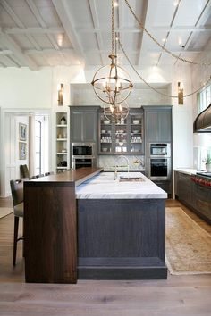Stunning kitchen features charcoal gray shaker cabinets paired with Calacatta Ondulato Marble countertops and backsplash.