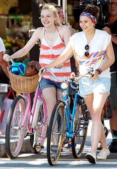 Dakota Fanning and Elizabeth Olsen walked their bikes shooting Very Good Girls (costarring Demi Moore) in NYC July 12.
