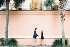 Chic couple walking in downtown Charleston in front of pink wall | Catherine Ann Photography | Kodak Portra 400
