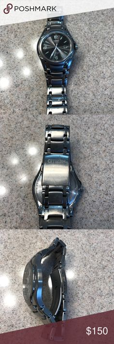 Men's Titanium Citizen Watch Men's Titanium Citizen ECO DRIVE watch with round black dial, with date feature, lumbrite markers at 1,2,4,5,7,8,10, and 11. Lumbrite numbers at 12, 6, and 9. Lumbrite minute, hour and second hand. Water Resistant to 100 Meters, bracelet style band with adjustable clasp. There are a few marks on the crystal and the band from wear. ECO DRIVE is powered by direct sunlight or inside lighting, there is no battery. Citizen Accessories Watches