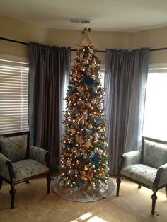 Christmas tree with blue, gold, silver and cream ornaments.