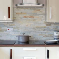 Natural coloured slate wall tiles are used complement this cream modern kitchen http://www.housetohome.co.uk/kitchen/picture/hi-gloss-cream-kitchen