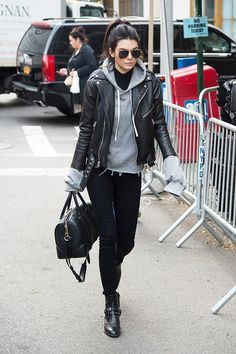 Kendall Jenner wears a gray hoodie, moto jacket, skinny jeans, Saint Laurent boots, Givenchy satchel, and aviator sunglasses