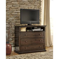 Keep your media essentials organized and out of the way with the Noremac media chest. Crafted with rich vintage casual appeal, this rustic chest is finished in dark brown and designed by Ashley Furniture with three storage drawers.