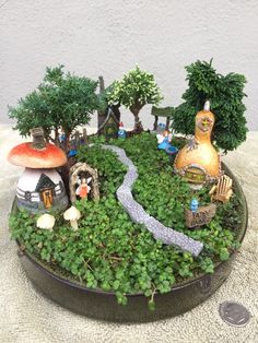 Miniature Fairy Garden - ON THE MICRO SIDE is a micro mini village -- fairies and gnomes live here. The micro fairy seen on the left is walking from her arbor to her cottage; the micro fairy seen on the right is checking the water level in her fountain. Farther down in the village, Mr. Gnome, on the bridge, is coming home from a hard day's work only to find Mrs. Gnome waiting for him. It is a good day at the village, ON THE MICRO SIDE. 5/2016