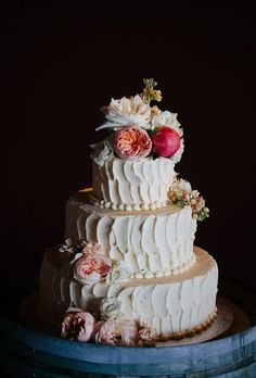 A beautiful buttercream wedding cake by Felicia's SweetFace Pastry Shoppe, topped with florals and fall fruit.