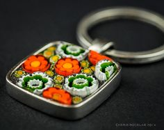 This keychain was created with murano millefiori.    The ring has a brass shank with a pewter bezel plated with .999 Fine Silver