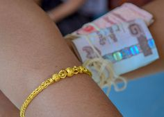 Offer of money and gold bracelet blessed by monk. Monk Blessed String Bracelets in Thailand (Sai Sin Sacred Thread). String blessed by monks to bring good luck and protection. Traditions and Culture in rural Thailand (Isaan) by http://potatoinrice.com/