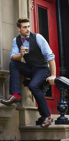 Comprar ropa de este look:  https://lookastic.es/moda-hombre/looks/chaleco-de-vestir-camisa-de-manga-larga-vaqueros-zapatos-con-doble-hebilla-corbatin-calcetines/4016  — Corbatín de Rayas Verticales Rojo y Blanco  — Camisa de Manga Larga Celeste  — Chaleco de Vestir Gris Oscuro  — Vaqueros Azul Marino  — Calcetines Rojos  — Zapatos con Doble Hebilla de Cuero Marrón Oscuro