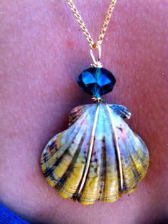 A huge 1and 1/4 moonrise shell wrapped with 14kt gold filled wire. Its paired with a lovely bluish- teal swarovski crystal bead, which brings