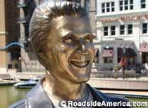"""Milwaukee, Wisconsin:  Statue of The Fonz.  Arthur """"The Fonz"""" Fonzarelli was a character in the sitcom Happy Days, set in Milwaukee during the 1950s.     On the Milwaukee River Walk just south of Wells Street. East side of river.  FROM THE NORTH: I-43 exit 72E. Drive south three blocks, then turn left onto Wells St. Drive three blocks, cross the river, and the Fonz will be on the far side, on the right."""