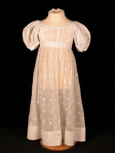 White muslin girls dress with white embroidered leaves. Wide neck, large short puff sleeves. Panel gathered at front bodice. 1820 (circa)