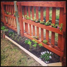 Valla y macetas de jardín con palets