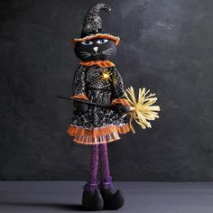 """Katrina the cat welcomes you to the spookiest time of the season! Fiber optics on front brim of hat and bottom of dress. Spider lights up. Uses 3 AA batteries (not included). 7 1/2"""" W x 6"""" diam. X 27"""" H. Polyester, wood. Imported.<br><br>For decorative use only. this is not a toy. Keep out of reach of children."""
